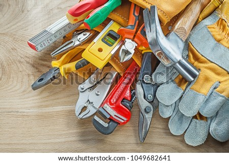 Tools in leather building belt on wooden board top view #1049682641