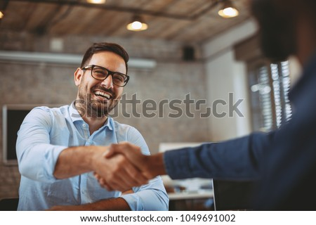 Close up of handshake in the office Royalty-Free Stock Photo #1049691002