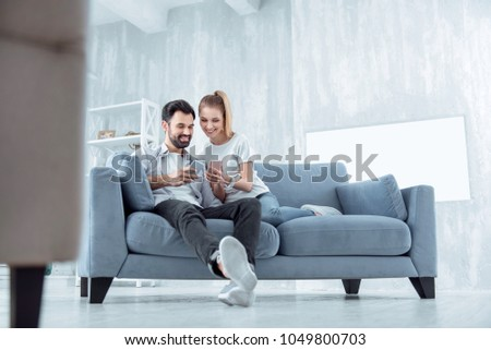 Just relax. Pleased female person keeping smile on her face and looking downwards while sitting near her boyfriend #1049800703