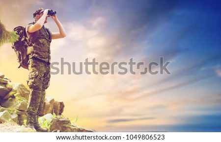 hunting, army, military service and people concept - young soldier with backpack looking to binocular over sky observing area