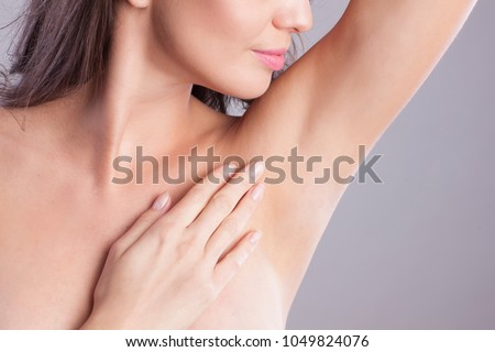 Close up of female armpit. Model touching her axilla. Royalty-Free Stock Photo #1049824076