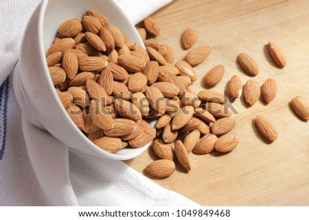 A bowl with bunch of organic almonds on a wooden desk, healthy food #1049849468
