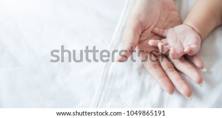 Asian parent hands holding newborn baby fingers, Close up mother's hand holding their new born baby. Love family healthcare and medical body part father's day concept panoramic banner #1049865191