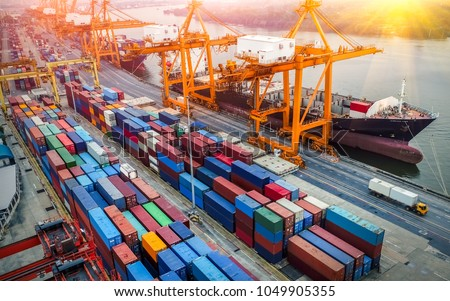 Logistics and transportation of Container Cargo ship and Cargo plane with working crane bridge in shipyard at sunrise, logistic import export and transport industry background Royalty-Free Stock Photo #1049905355