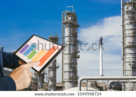 businessman fingers touching chart tablet against oil refinery in petrochemical Aerial view oil refinery night during twilight,Industrial zone,Energy power station  #1049908724