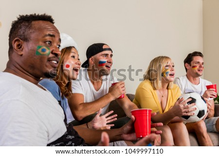 Multinational sports fans watching football on TV with cheer and excitement from couch #1049997110