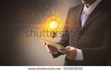 Business people working on tablet technology with floating light bulbs on top. #1050058502
