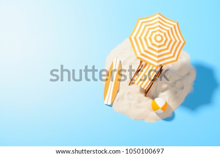 Tropical vacation background. Sun lounger with umbrella and beach accessories for active rest on the sandy island, copy space, top view #1050100697