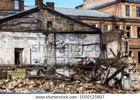 An abandoned house collapses in a poor neighborhood. The house is destroyed. Cracks in wall of house. Destruction of old houses, earthquakes, economic crisis, abandoned houses. Broken unfit house #1050125807