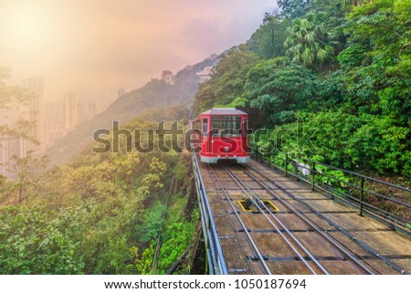 Tourist tram at the peak famous railroad train downtown on forest hill, Victoria peak tram and Hong Kong city skyline and skyscraper building construction architecture, Kowloon, Hong Kong, Asia. Royalty-Free Stock Photo #1050187694