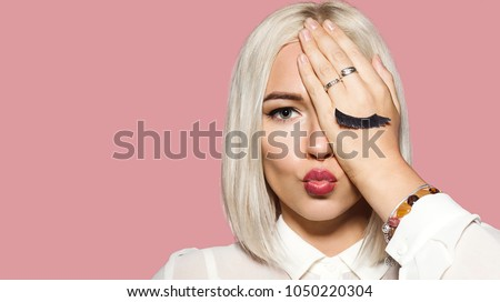 Young woman makes air kiss with her lips and closes one eye by hand. Blonde hair model in white shirt closed her eye with hand. Concept of fun and merriment. Studio portrait on pink background. #1050220304