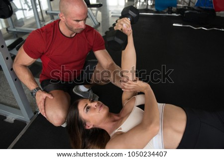 Young Couple Working Out In Gym - Doing Triceps Exercise With Dumbbells #1050234407