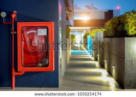 Fire Safety Concept, Fire extinguisher and fire hose reel in public building corridor #1050254174