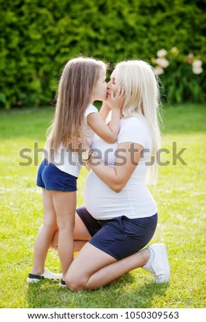 Beautiful pregnant woman and little daughter. Cute little girl  kissing her pregnant  mother  in summer nature.