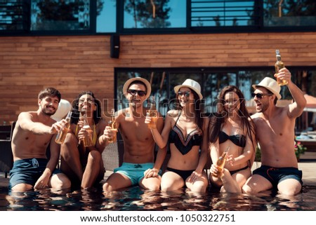 Company of young people having fun and enjoying summertime in aquapark. Swimming pool party. Summer vacation friends together at swimming pool. #1050322751