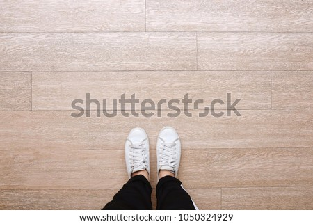 Selfie of feet in fashion sneakers on wooden floor background, top view with copy space #1050324929