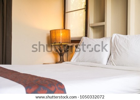 Comfortable pillow on bed decoration in hotel bedroom interior #1050332072