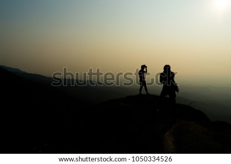 silhouette of a photographer taking pictures  #1050334526