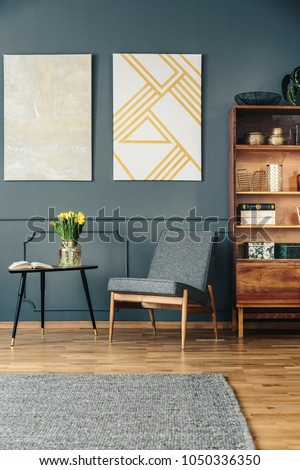 Gray, upholstered chair next to an elegant, wooden bookcase in a reading corner of a dark living room interior with molding #1050336350