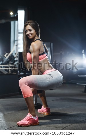 Beautiful strong sexy athletic muscular young caucasian fitness girl workout training in the gym on diet pumping up abs muscles and posing bodybuilding health care and fitness concept #1050361247