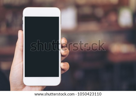 Mockup image of a hand holding white mobile phone with blank black desktop screen with blur background #1050423110