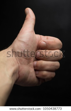 Thumbs up hand isolated on black background #1050438773