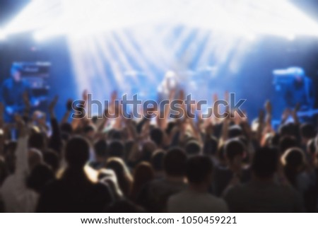 Concert crowd. Blurred silhouettes young people in front of bright stage lights. Music festival #1050459221