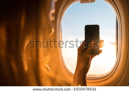 Taking photo on airplane,Travel accessories for snap moment,Hand holding Smart phone and take photograph,Camera for Travel accessories,Photography in the air.