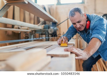 Attractive man doing woodwork in carpentry. Smiling woodworker. Man doing woodwork in carpentry. Carpenter work on wood plank in workshop. Carpenter doing his job in carpentry workshop. #1050483146