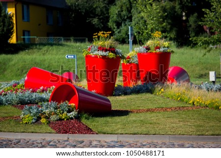 Street landscape design, flower city decoration. Red pots with flowers and plants #1050488171