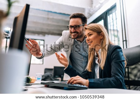 Working together on project. Two young business colleagues working on computer Royalty-Free Stock Photo #1050539348