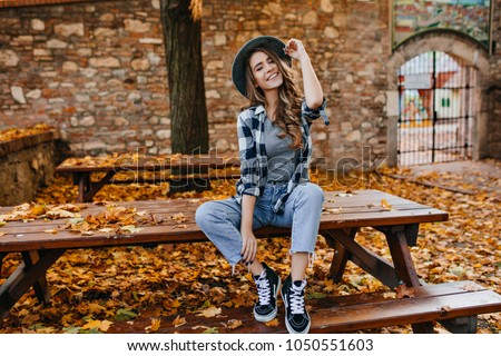 Carefree young woman in trendy vintage pants sitting on table in park and laughing. Curly cute girl in good mood posing in autumn day, enjoying good weather. #1050551603