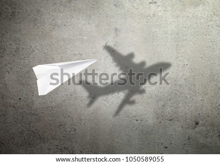 Paper plane in mid flight with shadow of a real plane #1050589055