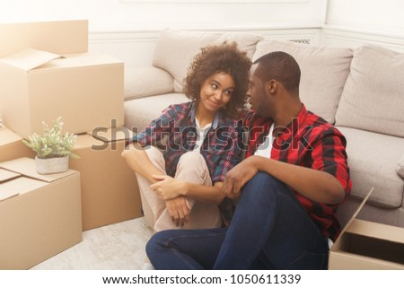 Happy african-american couple unpacking moving boxes in new apartment, copy space #1050611339