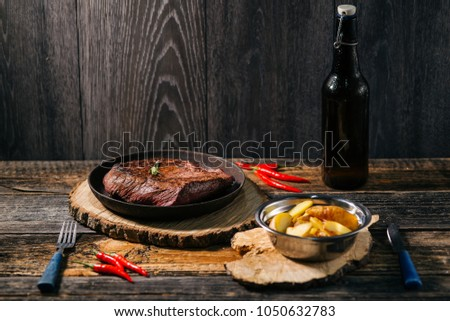 Grilled beef steak with spices on round board with potato fork , knife and craft beer #1050632783