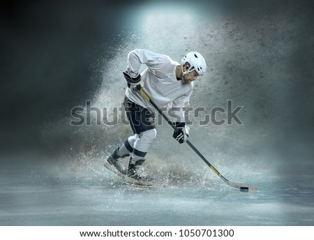 Caucassian ice hockey Player in dynamic action in a professional sport game play on the laptop in hockey under stadium lights. #1050701300