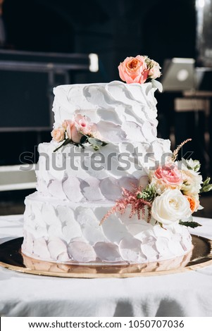 Wedding cake. Close-up photo of a beautiful white three-tiered wedding cake decorated by flowers and greenery