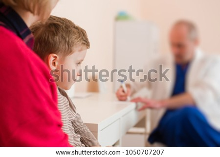 Child in mama hugs with kid doctor writing background #1050707207