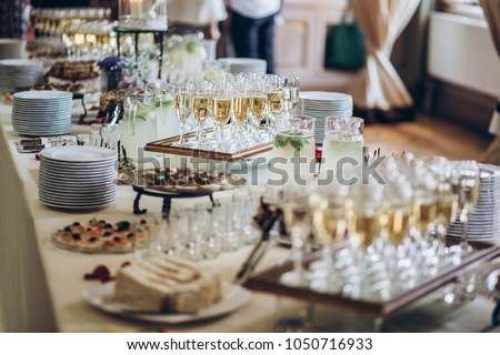 stylish champagne glasses and food  appetizers on table at wedding reception. luxury catering at celebrations. serving food and drinks at events concept #1050716933