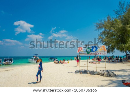 PODA, THAILAND - FEBRUARY 09, 2018: Outdoor view of unidentified people posing for a pictures in front of informative sign over the white sand on Poda island in a gorgeous sunny day #1050736166