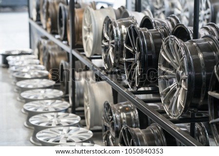 Various alloy wheels in store, selective focus. Car alloy wheels at a wheel shop. #1050840353