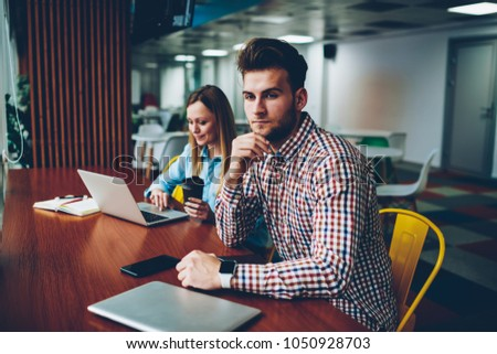 Thoughtful young man in casual shirt thinking on idea for coursework while hipster girl with tasty coffee searching information on websites on laptop computer connected to wireless internet #1050928703