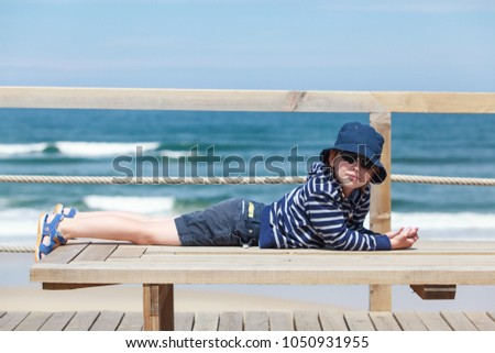 Kid boy wearing sunglasses and cap relax on the beach  #1050931955