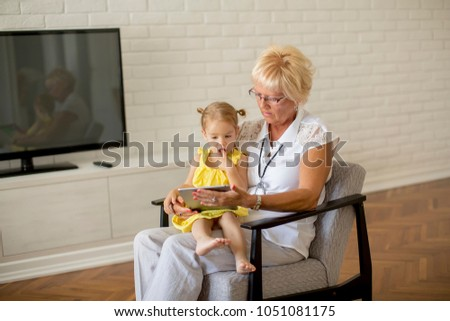 Grandmother reading book to little granddaughter in the room #1051081175