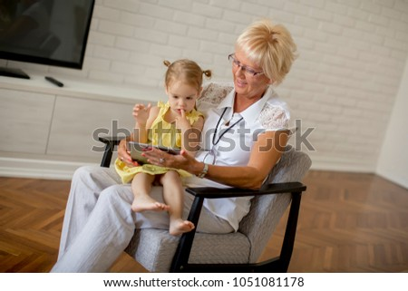 Grandmother reading book to little granddaughter in the room #1051081178