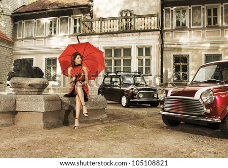 Vintage image of young attractive girl with two old cars