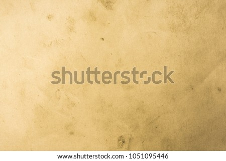 Blank aged paper sheet as old dirty frame background with dust and stains. Front view. Vintage and antique art concept. Detailed closeup studio shot. Sepia toned #1051095446