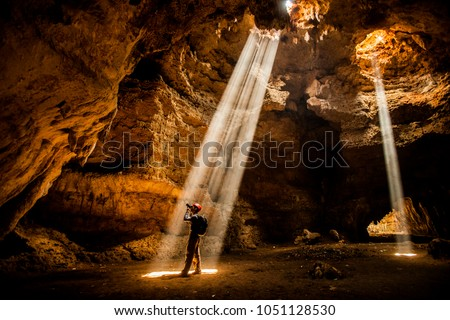 Man in the cave exploration with Ray of light Royalty-Free Stock Photo #1051128530