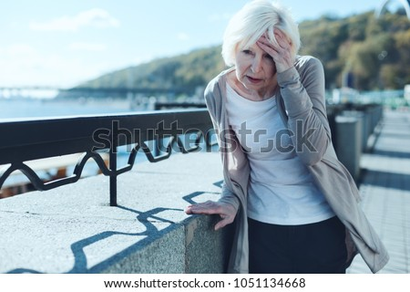 Need to take my pills. Exhausted older lady leaning on a barrier and touching her forehead while suffering from a terrible headache outdoors. #1051134668