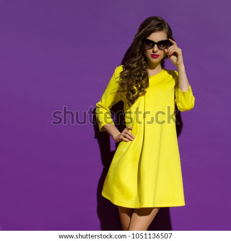 Beautiful young woman in yellow mini dress and sunglasses. Three quarter length studio shot on purple background. #1051136507